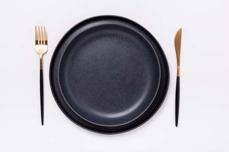 Two empty black ceramic plates and cutlery on white background. Top view - Image