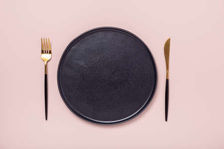 Black ceramic plate, fork and knife on pastel pink background. Top view. Place for text - Image
