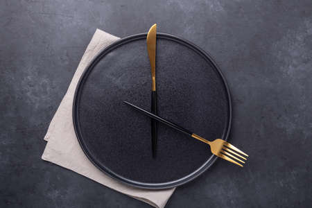 Empty ceramic plate and cutlery on dark stone background Copy space Top view - Image