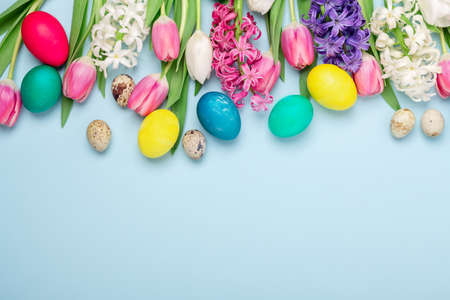 Multicolored eggs and spring flowers tulips and hyacinths on a blue background. Easter concept. Copy space - Image
