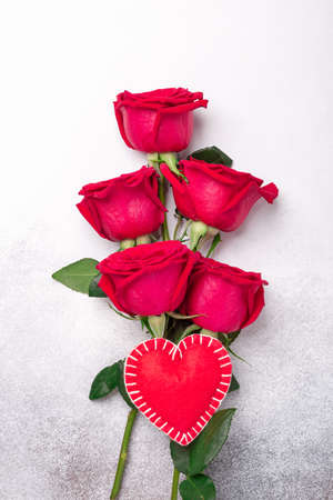 Valentines day greeting card. Red roses and decorative textile heart on stone background. Top view. Vertical - Image