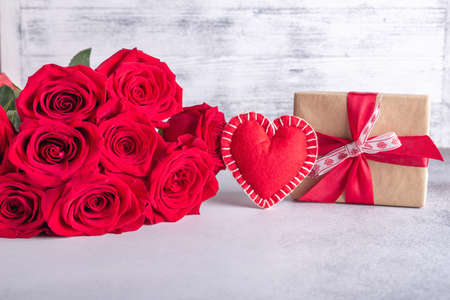 Beautiful red roses, gift box and decorative textile heart on stone background. Valentine's day concept - Image