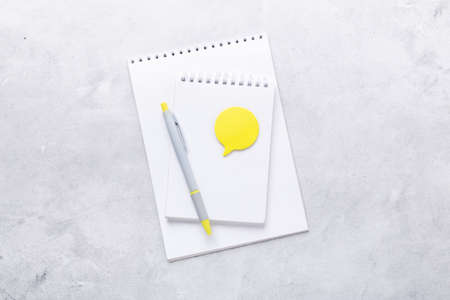 Office workplace. Notepad with pen and yellow sticker on gray stone background. Flat lay. Top view - Image