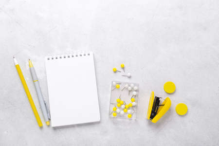 Gray workspace with notepad and yellow stationery accessories. Illuminating Yellow and Ultimate Gray, colors of the year 2021 - Image