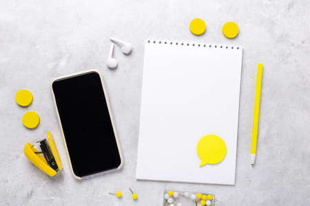 Office workplace with smartphone, notepad and stationery accessories on gray stone background. Yellow stationery. Flat lay. Top view - Image