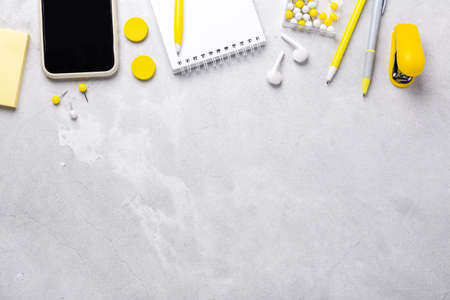 Top view of workspace with smartphone, notepad and stationery accessories on gray stone background. Illuminating Yellow and Ultimate Gray, colors of the year 2021 - Image
