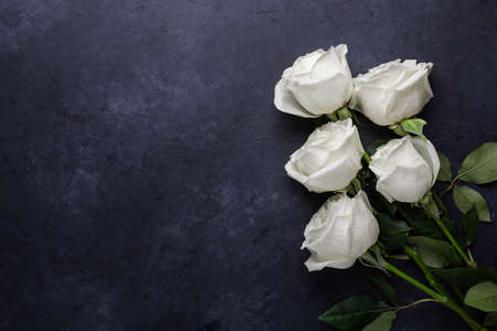 White rose flowers bouquet on black stone background Valentines day greeting card Copy space Flat lay