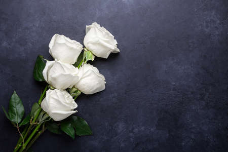 White rose flowers bouquet on black stone background. Greeting card with copy space for text - Image