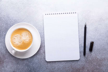 Office desk with cup of coffee, note pad, smartphone and supplies. Top view. Copy space - Image 版權商用圖片