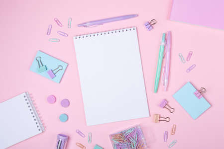 Top view of workspace with notepad and stationery accessories on pink background. Back to school concept - Image