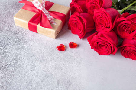 Beautiful red roses, gift box and decorative hearts on stone background. Valentine's day concept - Image