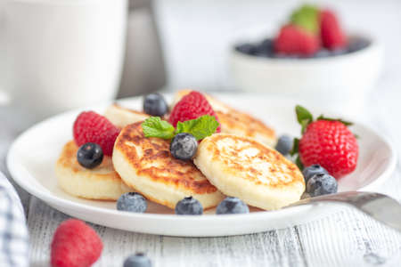 Close up of cottage cheese pancakes with fresh berries on white wooden table. Curd fritters with berries, syrniki. Soft focus - Image Stock fotó