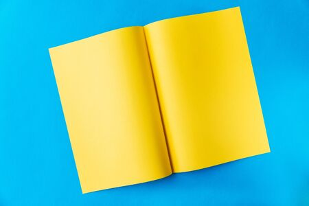 Yellow sheet of A3 paper folded in the middle in a spread on a blue background with a place for text Stock Photo