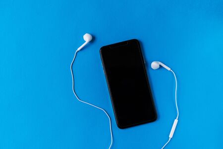 Modern mobile phone with a dark screen off with wired white headphones around it on a blue background. Good wallpaper. Popular picture. Top view. Lifestyle for active young people