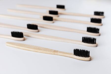 Group of black eco bamboo toothbrushes, on white background. Top view, pattern. Natural organic product for oral hygiene. Dental zero waste and no plastic concept. Safe for the earth. Close-up.