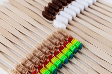 Group of eco bamboo toothbrushes, on white background. Different color. Top view, pattern. Natural organic product for oral hygiene. Dental zero waste and no plastic concept. Safe for the earth.