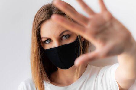 Portrait en gros plan d'une jeune femme surprise dans un masque médical noir et un t-shirt blanc sur fond clair, avec la main au premier plan. Période de quarantaine de l'épidémie de coronavirus. Concept de séjour à la maison