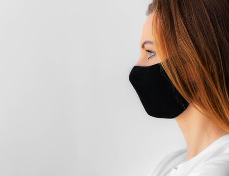Close-up profile of a young woman in a black medical mask and white t-shirt on a light background. Quarantine of coronavirus epidemic just ended, covid-19. Stay home concept. Virus protection