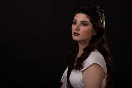 Close-up portrait of a archer woman in white dress on black background. Greek goddess Artemis. Studio photo shoot. Professional makeup and hairstyle for a brunette with long dark hair. Young woman