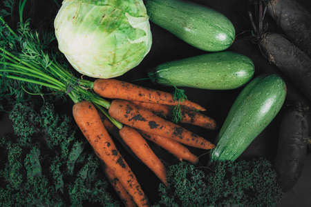 A collection of organic vegetables collected from the garden. Organic eco food. Healthy diet. Freshly picked vegetables. Fresh greens for salad. Natural organic food. Edible vegetable background.