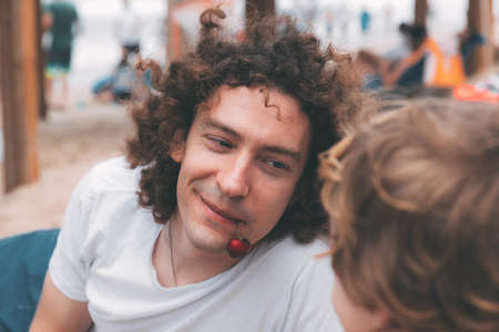 Father's day. Dad and son. Little son feeds dad ripe cherries on the beach. Happy family father and child. Young handsome man with long curly hair smiles and his son in the foreground from back