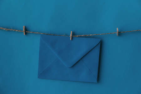 One closed blue envelope hanging on rope isolated blue background. Write a letter to a friend. Postal envelope. Gift envelope for postcards.