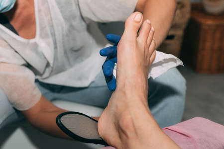 Peeling feet pedicure procedure in salon. Hardened leather grater. Leg of a young woman in Spa. Peeling of heels. Professional pedicure process. Concept of beauty care and health.