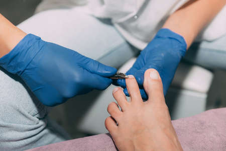 Pedicure process in salon. Foot care treatment and nail. Removing dead skin with forceps. Master in blue gloves makes pedicure with manicure machine. Concept of beauty care and health. 写真素材