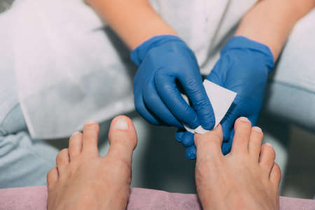 Pedicure process in salon. Foot care treatment and nail. Degreasing nails with a cloth and solution. Master in blue gloves makes pedicure with manicure machine. Concept of beauty care and health.