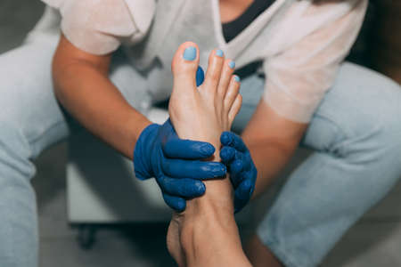 Close-up of Pedicure in salon. Foot care treatment and nail. Foot massage during the pedicure process. Master in blue gloves makes pedicure with manicure machine. Concept of beauty care and health