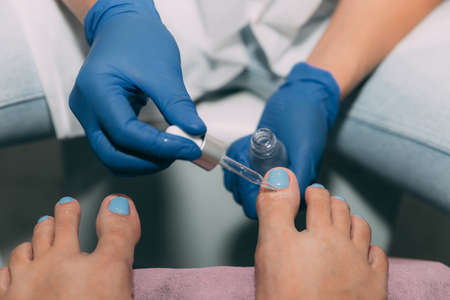 Pedicure in salon. Foot care treatment and nail. Applying oil from a pipette at the end of a pedicure. Master in blue gloves makes pedicure with manicure machine. Concept of beauty care and health