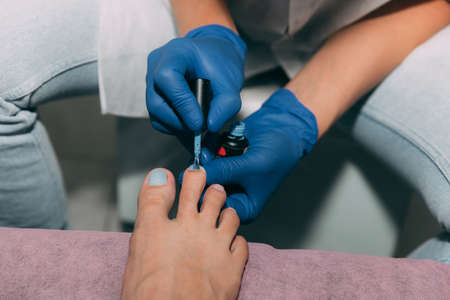 Pedicure process in salon. Foot care treatment and nail. Applying gel polish to nails with a brush. Master in blue gloves makes pedicure with manicure machine. Concept of beauty care and health.