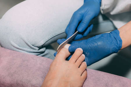 Pedicure process in salon. Foot care treatment and nail. File filing with a nail file. Master in blue gloves makes pedicure with manicure machine. Concept of beauty care and health.