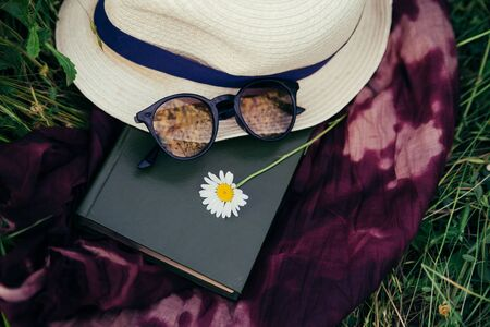 A summer hat, sunglasses, a chamomile flower and a book lie on a bright scarf among a green field. Concept of summer holidays or preparing for studies Zdjęcie Seryjne