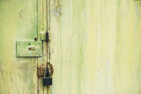 Abstract colorful wall texture and background. Close-up iron surface with yellow paint and the padlock