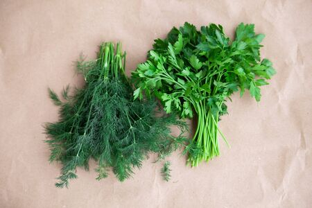 Two fresh bunches of greenery on craft paper. The concept of summer harvest and healthy nutrition. Dill and parsley. View from above