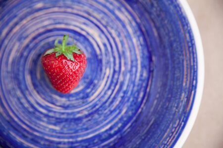 One berry of ripe strawberry on a bright blue dish. Healthy eating concept. Flat lay