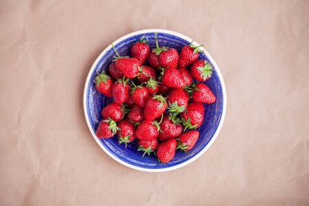 Bright blue dish with ripe strawberries. View from above. Concept of summer mood and healthy eating. Zdjęcie Seryjne