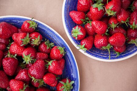 Two bright blue plates with ripe strawberries. View from above. Healthy eating concept