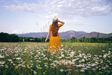 A young girl in a yellow dress stands in a daisy field among flowers and spikelets. The concept of summer days and traveling
