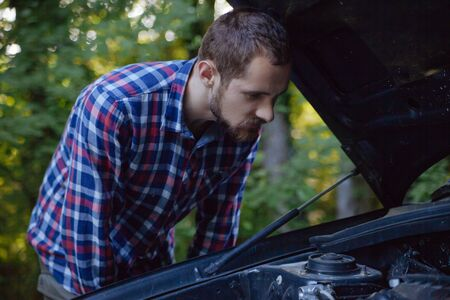 The guy opened the hood of the car and looks at the engine. Emergency stop and car repair Zdjęcie Seryjne