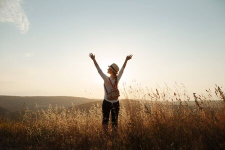 A young girl in a hat and a backpack stands on top of the mountain and raised her hands to the sky