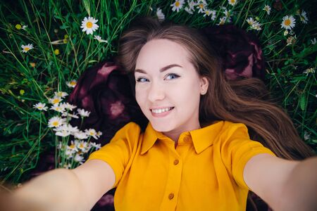 Cute girl in a bright yellow dress lies among a flower field and makes a selfie