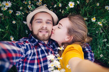 A girl in a bright yellow dress kisses a guy in a plaid shirt. They make selfie together