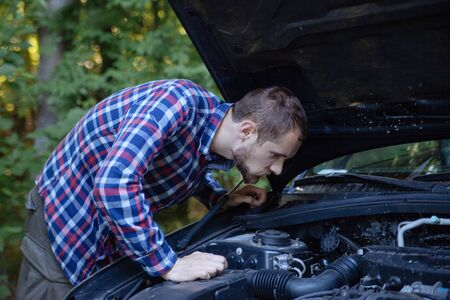 The guy opened the hood of the car and looks at the engine. Emergency stop and car repair Stock fotó
