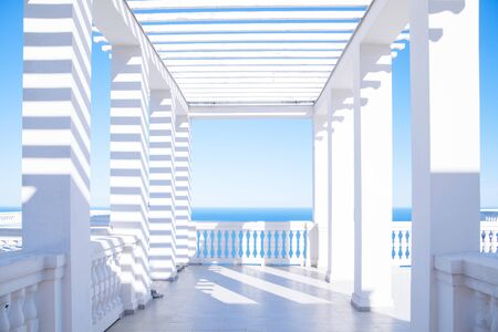White terrace flooded with sunlight overlooking the bright blue sea Zdjęcie Seryjne