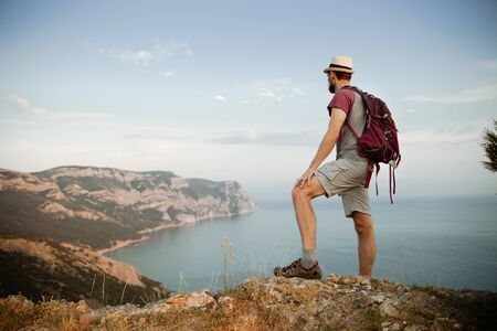 The traveler stands on a stone and looks at the mountains and the sea. Summer hiking concept