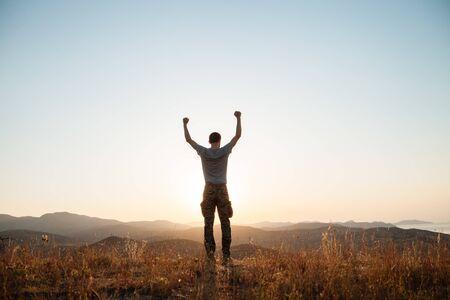 Le gars se tient parmi les montagnes et lève les bras dans un geste victorieux.