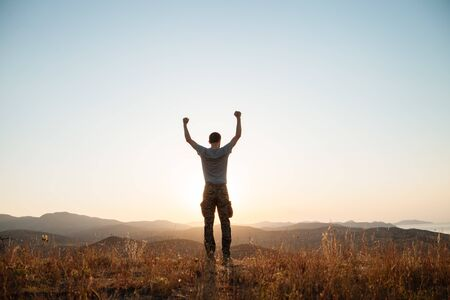The guy stands among the mountains and raise his arms in a victorious gesture.