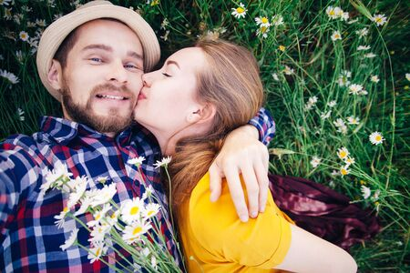 A girl in a bright yellow dress kisses a guy in a plaid shirt. Lovely couple on a summer flower field
